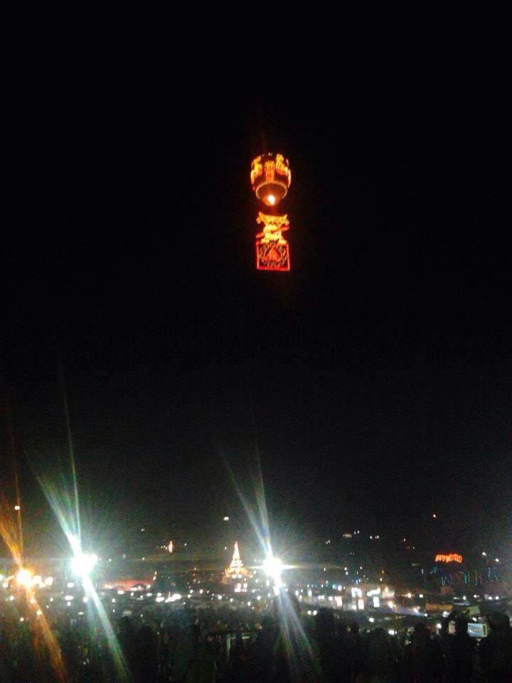 オレンジ色にひかる気球が夜空に上がっている様子